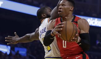 Houston Rockets' Russell Westbrook, right, looks to shoot past Golden State Warriors' Eric Paschall in the first half of an NBA basketball game Thursday, Feb. 20, 2020, in San Francisco. (AP Photo/Ben Margot)