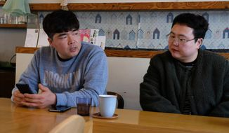 "In this Wednesday, Feb. 19, 2020, photo, props manager Joo Dong-man, left, speaks as costume manager Yang Hee-hwa listens during an interview at a cafe in Ilsan, South Korea. South Korea's latest hit drama ""Crash landing on you"" portrays the fantastical story of a billionaire heiress accidentally paragliding into North Korea and falling in love with army captain. (AP Photo/Juwon Park)"