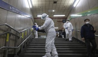 """Workers wearing protective gears spray disinfectant as a precaution against the coronavirus at a subway station in Seoul, South Korea, Friday, Feb. 21, 2020. South Korea on Friday declared a """"special management zone"""" around a southeastern city where a surging viral outbreak, largely linked to a church in Daegu, threatens to overwhelm the region's health system. (AP Photo/Ahn Young-joon)"""