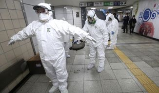 """Workers wearing protective gears help clean each other's suits after disinfecting as a precaution against the coronavirus at a subway station in Seoul, South Korea, Friday, Feb. 21, 2020. South Korea on Friday declared a """"special management zone"""" around a southeastern city where a surging viral outbreak, largely linked to a church in Daegu, threatens to overwhelm the region's health system. (AP Photo/Ahn Young-joon)"""