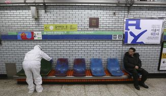 """A worker wearing protective gears disinfect chairs as a precaution against the coronavirus at a subway station in Seoul, South Korea, Friday, Feb. 21, 2020. South Korea on Friday declared a """"special management zone"""" around a southeastern city where a surging viral outbreak, largely linked to a church in Daegu, threatens to overwhelm the region's health system. (AP Photo/Ahn Young-joon)"""