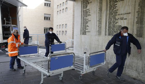 FILE - In this Friday, Feb. 21, 2020, file photo, personnel carry new beds inside a hospital of Codogno, near Lodi in Northern Italy. Health officials reported the country's first cases of contagion of COVID-19 in people who had not been in China. Italy saw cases of the new virus more than quadruple in a day as it grapples with infections in a northern region that apparently have spread through a hospital and a cafe. (AP Photo/Luca Bruno)