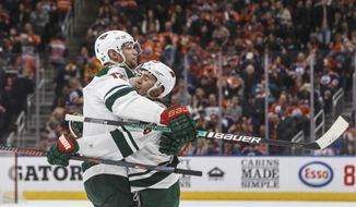 Minnesota Wild's Eric Staal (12) and Jared Spurgeon (46) celebrate a goal against the Edmonton Oilers during the third period of an NHL hockey game Friday, Feb. 21, 2020, in Edmonton, Alberta. (Jason Franson/The Canadian Press via AP)