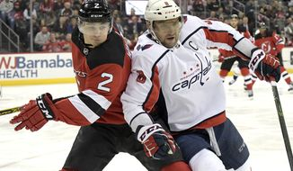 Washington Capitals left wing Alex Ovechkin (8) and New Jersey Devils defenseman Colton White (2) chase after the puck during the first period of an NHL hockey game Saturday, Feb. 22, 2020, in Newark, N.J. (AP Photo/Bill Kostroun)