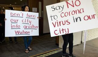Mary Cahill, left, leaves a news conference where officials discussed the proposal for housing coronavirus patients at the Fairview Development Center in Costa Mesa, Calif., Saturday, Feb. 22, 2020. A court temporarily blocked the U.S. government from sending up to 50 people infected with a new virus from China to the Southern California city for quarantine after local officials argued that the plan lacked details about how the community would be protected from the outbreak. (Mindy Schauer/The Orange County Register via AP)