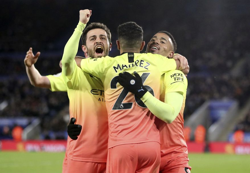 Manchester City's Gabriel Jesus, right, celebrates scoring his side's first goal of the game against Leicester with team mates Riyad Mahrez, centre, and Mota Bernardo Silva during their English Premier League soccer match at the King Power Stadium in Leicester, England, Saturday Feb. 22, 2020. (Nick Potts/PA via AP)