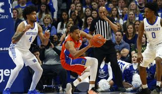 Florida's Kerry Blackshear Jr., middle, stumbles between Kentucky's Nick Richards (4) and Ashton Hagans (0) in the first half of an NCAA college basketball game in Lexington, Ky., Saturday, Feb. 22, 2020. (AP Photo/James Crisp)