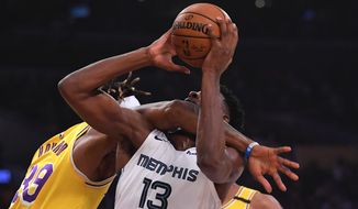 Los Angeles Lakers center Dwight Howard, left, fouls Memphis Grizzlies forward Jaren Jackson Jr. (13) in the act of shooting during the first half of an NBA basketball game Friday, Feb. 21, 2020, in Los Angeles. (AP Photo/Mark J. Terrill)