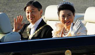 FILE - In this Nov. 10, 2019, file photo, Japanese Emperor Naruhito, left, and Empress Masako wave during the royal motorcade in Tokyo. Emperor Naruhito turns 60 years old Sunday, Feb. 23, 2020. (AP Photo/Eugene Hoshiko)