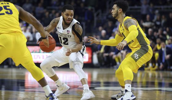 Providence's Luwane Pipkins (12) is defended by Marquette's Koby McEwen (25) and Markus Howard, right, during the second half of an NCAA college basketball game Saturday, Feb. 22, 2020, in Providence, R.I. (AP Photo/Stew Milne)