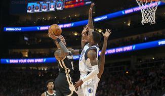 Atlanta Hawks forward John Collins (20) shoots past Dallas Mavericks guard Delon Wright (55) in the first half of an NBA basketball game Saturday, Feb. 22, 2020, in Atlanta, Ga. (AP Photo/Brett Davis)