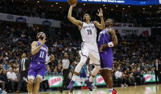 Brooklyn Nets guard Spencer Dinwiddie, center, shoots between Charlotte Hornets forward Cody Martin (11) and Charlotte Hornets center Bismack Biyombo (8) in the first half of an NBA basketball game in Charlotte, N.C., Saturday, Feb. 22, 2020. (AP Photo/Nell Redmond)