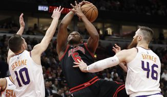 Chicago Bulls forward/center Cristiano Felicio, center, rebounds a ball against Phoenix Suns guard Ty Jerome, left, and center Aron Baynes during the first half of an NBA basketball game in Chicago, Saturday, Feb. 22, 2020. (AP Photo/Nam Y. Huh)