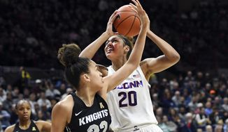Connecticut's Olivia Nelson-Ododa (20) shoots over Central Florida's Brittney Smith (32) during the first half of an NCAA college basketball game Saturday, Feb. 22, 2020, in Storrs, Conn. (AP Photo/Stephen Dunn)