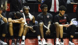 San Diego State players sit on the bench during the second half of an NCAA college basketball game against UNLV, Saturday, Feb. 22, 2020, in San Diego. UNLV won 66-63. (AP Photo/Denis Poroy)