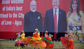 Indian folk dancers rehearse before a billboard featuring Indian Prime Minister Narendra Modi, President Trump and first lady Melania Trump. (Associated Press)