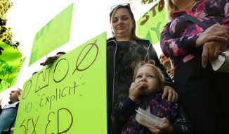 Vicktoryia Seliuzhytskaya, looks down as her daughter Magdlene, 2, eats a snack during a rally to protest proposed changes to sex education guidance for teachers, Wednesday, May 8, 2019, in Sacramento, Calif. The California State Board of Education is set to vote Wednesday on new guidance for teaching sex education in public schools. The guidance is not mandatory but it gives teachers ideas about how to teach a wide range of health topic including speaking to children about gender identity. (AP Photo/Rich Pedroncelli) **FILE**