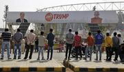 """Indians watch workers fix a billboard at an entrance of Sardar Patel stadium ahead of the visit of U.S. President Donald Trump in Ahmedabad, India, Sunday, Feb. 23, 2020. Trump is visiting the city in Gujarat during a two-day trip to India to attend an event called """"Namaste Trump,"""" which translates to """"Greetings, Trump,"""" at a cricket stadium along the lines of a """"Howdy Modi"""" rally attended by Indian Prime Minister Narendra Modi in Houston last September. (AP Photo/Ajit Solanki)"""