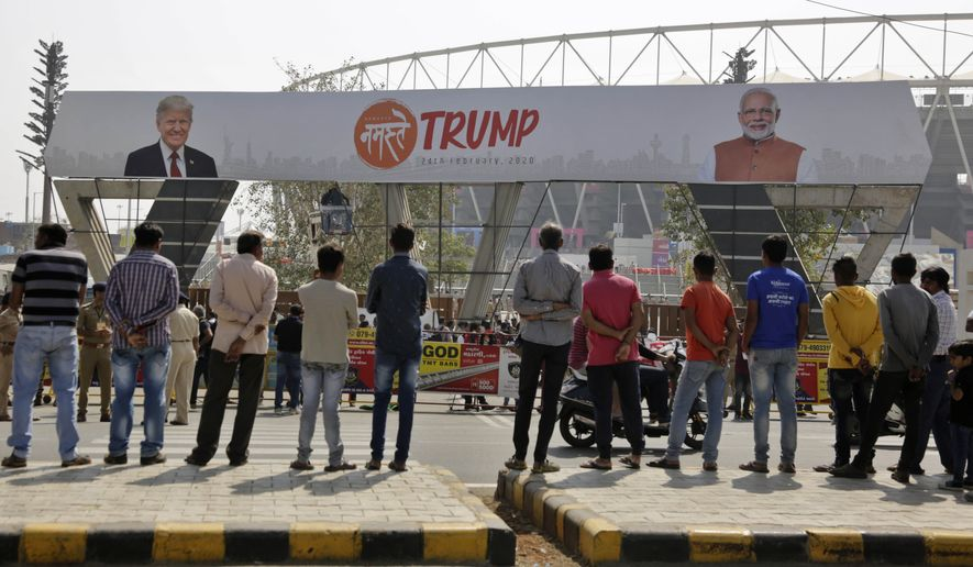"Indians watch workers fix a billboard at an entrance of Sardar Patel stadium ahead of the visit of U.S. President Donald Trump in Ahmedabad, India, Sunday, Feb. 23, 2020. Trump is visiting the city in Gujarat during a two-day trip to India to attend an event called ""Namaste Trump,"" which translates to ""Greetings, Trump,"" at a cricket stadium along the lines of a ""Howdy Modi"" rally attended by Indian Prime Minister Narendra Modi in Houston last September. (AP Photo/Ajit Solanki)"