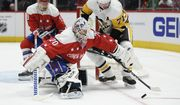 Washington Capitals goaltender Braden Holtby (70) and Pittsburgh Penguins center Evgeni Malkin (71) battle for the puck during the first period of an NHL hockey game, Sunday, Feb. 23, 2020, in Washington. Also seen is Capitals defenseman Dmitry Orlov (9). (AP Photo/Nick Wass)