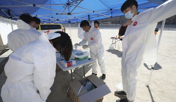 """Paramedics put on protective gear to inspect people possibly infected with the coronavirus in Daegu, South Korea, Sunday, Feb. 23, 2020. South Korea's president has put the country on its highest alert for infectious diseases and says officials should take """"unprecedented, powerful"""" steps to fight a viral outbreak. (Kim Hyun-tai/Yonhap via AP)"""