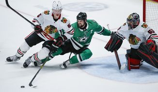 Dallas Stars forward Tyler Seguin (91) reaches for the puck as Chicago Blackhawks defenseman Connor Murphy (5) and goaltender Corey Crawford (50) defend during the second period of an NHL hockey game, Sunday, Feb. 23, 2020, in Dallas. (AP Photo/Brandon Wade)