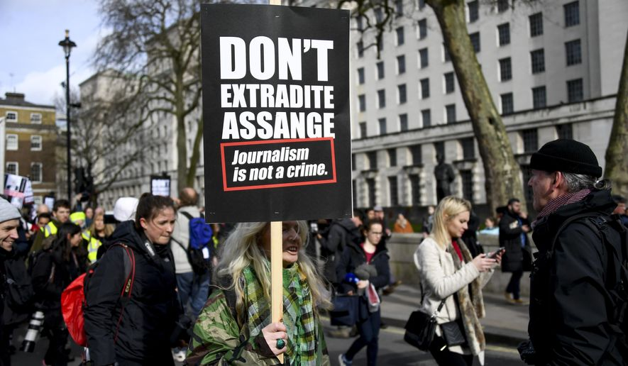 Demonstrators march to protest against the extradition of Wikileaks founder Julian Assange, in London, Saturday, Feb. 22, 2020. Assange is fighting extradition to the United States on spying charges.(AP Photo/Alberto Pezzali)