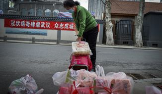 "In this Saturday, Feb. 22, 2020, photo, a woman using a trolley bag to collect foods distributed by volunteers outside her home in Wuhan in central China's Hubei province. South Korea and China both reported a rise in new virus cases on Sunday, as the South Korean prime minister warned that the fast-spreading outbreak linked to a local church and a hospital in the country's southeast had entered a ""more grave stage."" (Chinatopix via AP)"