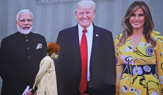 An elderly man walks past a giant hoarding welcoming U.S. President Donald Trump in Agra, India, Sunday, Feb. 23, 2020. Trump and the First Lady Melania Trump will be visiting Taj Mahal during their visit two-day trip to India. (AP Photo/Rajesh Kumar Singh)