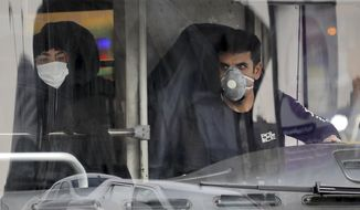 A public bus driver, right, and a commuter wear masks to help guard against the Coronavirus in downtown Tehran, Iran, Sunday, Feb. 23, 2020. On Sunday Iran's health ministry raised the death toll from the new virus to 8 people in the country, amid concerns that clusters there, as well as in Italy and South Korea, could signal a serious new stage in its global spread. (AP Photo/Ebrahim Noroozi)