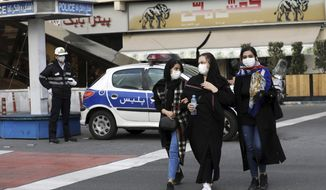 A policeman and pedestrians wear masks to help guard against the Coronavirus, in downtown Tehran, Iran, Sunday, Feb. 23, 2020. On Sunday, Iran's health ministry raised the death toll from the new virus to 8 people in the country, amid concerns that clusters there, as well as in Italy and South Korea, could signal a serious new stage in its global spread. (AP Photo/Ebrahim Noroozi)