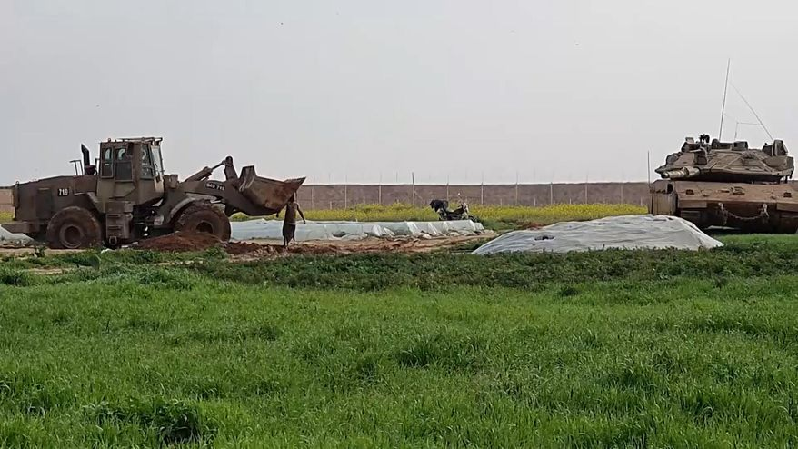 In this frame grab from video, an Israeli military vehicle removes the body of a Palestinian after he was shot and killed by soldiers, along the Gaza-Israel border, Sunday, Feb. 23, 2020. The Israeli military said it shot two Palestinian militants trying to place an explosive device along the border with Gaza, and Palestinian official said one of them was killed. The Hamas militant group accused Israel of abusing the corpse. The incident comes amid a relative lull along the security fence separating Israel from Gaza. (AP Photo)