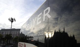 The Duomo gothic cathedral is reflected in a bus of fashion buyers in Milan, Italy, Sunday, Feb. 23, 2020. A dozen Italian towns saw daily life disrupted after the deaths of two people infected with the virus from China and a pair of case clusters without direct links to the outbreak abroad. A rapid spike in infections prompted authorities in the northern Lombardy and Veneto regions to close schools, businesses and restaurants and to cancel sporting events and Masses. (AP Photo/Luca Bruno)