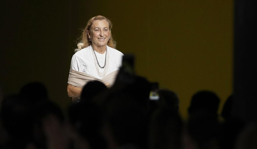 In this Sept. 20, 2018 file photo, Italian designer Miuccia Prada smiles after presenting her women's 2019 Spring-Summer collection, unveiled during the Fashion Week in Milan, Italy. Miuccia Prada and Raf Simons are entering in a creative design collaboration at Prada going forward indefinitely, the designers announced Sunday, Feb. 23, 2020 at a press conference on the sidelines of Milan Fashion Week. (AP Photo/Antonio Calanni, File)