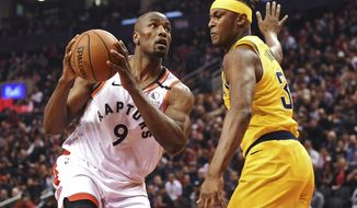 Toronto Raptors center Serge Ibaka (9) drives against Indiana Pacers center Myles Turner (33) during first-half NBA basketball game action in Toronto, Sunday, Feb. 23, 2020. (Frank Gunn/The Canadian Press via AP)