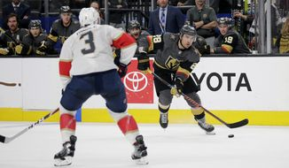 Vegas Golden Knights left wing William Carrier (28) looks to shoot the puck as Florida Panthers' Keith Yandle defends during the second period of an NHL hockey game Saturday, Feb. 22, 2020, in Las Vegas. (AP Photo/Marc Sanchez) ///