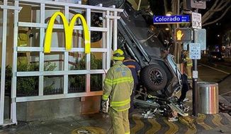 In this early Sunday, Feb. 23, 2020 photo released by the Santa Monica Fire Department shows a vehicle that plunged into the sidewalk in Santa Monica, Calif. A man was hospitalized after driving his Jeep off the the sixth floor of a Los Angeles-area parking garage. Responding officers found the destroyed vehicle up against a McDonald's restaurant across the street from the public parking structure. The 20-year-old driver was conscious and speaking with officers when they arrived. He was transported in critical condition. Fire officials say two passengers inside the Jeep were able to jump out before it went off the roof. The cause of the crash is under investigation. (Santa Monica Fire Department via AP)