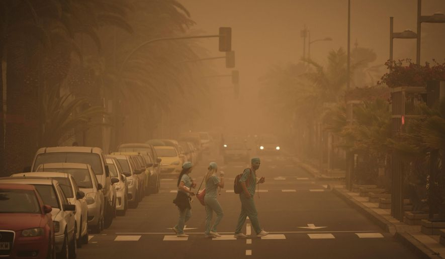 People in carnival dress walk across a street crossing in a cloud of red dust in Santa Cruz de Tenerife, Spain, Sunday, Feb. 23, 2020. Flights leaving Tenerife have been affected after storms of red sand from Africa's Saharan desert hit the Canary Islands and carnival was finally cancelled it was announced. (AP Photo/Andres Gutierrez)