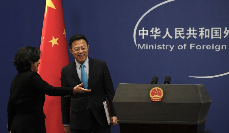 Chinese Foreign Ministry spokeswoman Hua Chunying, left, shows the way to their new spokesman Zhao Lijian on stage during a daily briefing at the Ministry of Foreign Affairs office in Beijing, Monday, Feb. 24, 2020. China's foreign ministry on Monday said it didn't matter that three expelled journalists had nothing to do with a Wall Street Journal editorial that Beijing deemed racist, and called on the paper to apologize. (AP Photo/Andy Wong) **FILE**
