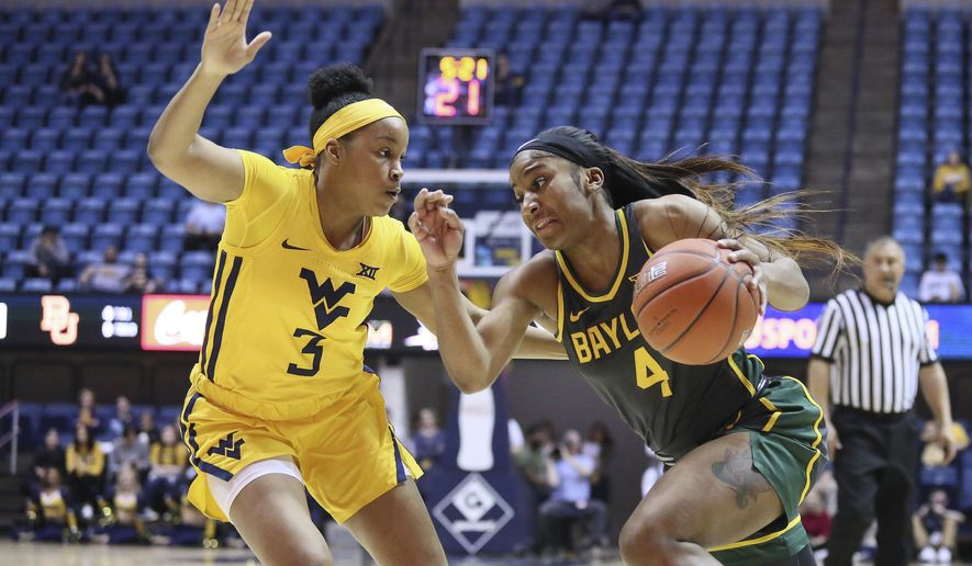 Baylor guard Te'a Cooper (4) goes upcourt while defended by West Virginia guard Kirsten Deans (3) during the first half of an NCAA college basketball game Monday, Feb. 24, 2020, in Morgantown, W.Va. (AP Photo/Kathleen Batten)
