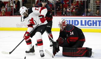 New Jersey Devils' Wayne Simmonds (17) tries to control the puck in front of Carolina Hurricanes goaltender Petr Mrazek (34), of the Czech Republic, during the third period of an NHL hockey game in Raleigh, N.C., Friday, Feb. 14, 2020. (AP Photo/Karl B DeBlaker)