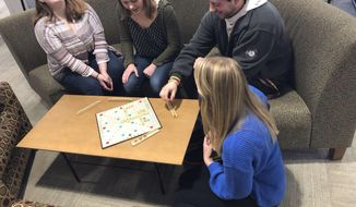 In this Tuesday, Feb. 18, 2020, photo, Paige Wagner, Kelly Gilomen, Trevor Peterson and Kendra Kvebak, who created Connection Day, play a game of Scrabble at the University of Minnesota Duluth in Duluth, Minn. They encouraged students to connect with one another face to face, rather than through their digital devices. (Dan Kraker/Minnesota Public Radio via AP)