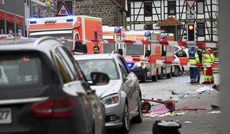 Emergency cars stand next to the scene of the accident with a car that is said to have crashed into a carnival parade in Volkmarsen, central Germany, Monday, Feb. 24, 2020. Several people have been injured, according to the police. The driver had been arrested by the police. (Uwe Zucchi/dpa via AP)