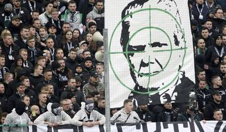 Supporters of Moenchengladbach show a banner with the portrait of Dietmar Hopp during the German Bundesliga soccer match between Borussia Moenchengladbach and TSG Hoffenheim in Moenchengladbach, Germany, Saturday, Feb. 24, 2020. Borussia Mönchengladbach supporters were the center of attention for targeting Hoffenheim's billionaire backer Dietmar Hopp with crude abusive messages during their sides' Bundesliga game on Saturday. It led to a suspension in play, but their actions were quickly condemned by fellow fans before the game could be called off. ( Roland Weihrauch/dpa via AP)