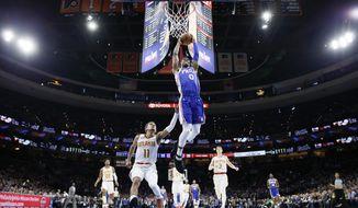 Philadelphia 76ers' Josh Richardson (0) goes up for a dunk past Atlanta Hawks' Trae Young (11) during the first half of an NBA basketball game, Monday, Feb. 24, 2020, in Philadelphia. (AP Photo/Matt Slocum)