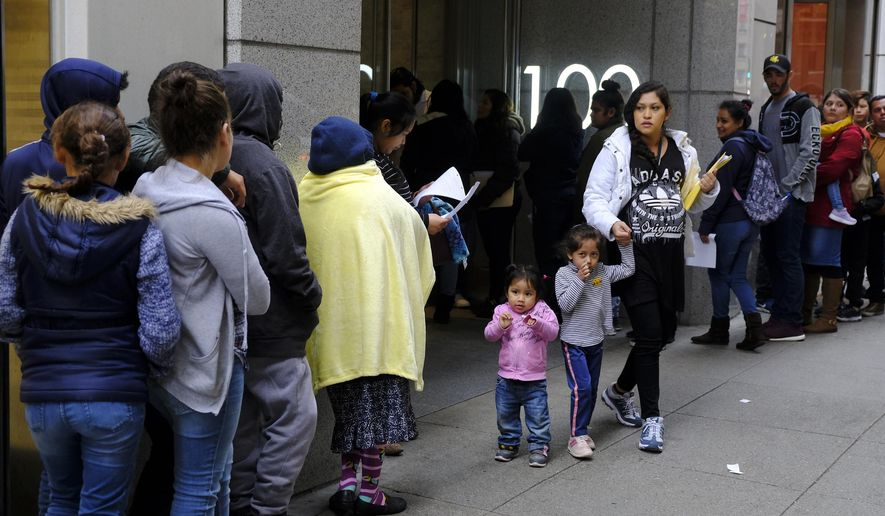FILE - In this Jan. 31, 2019, file photo, hundreds of people overflow onto the sidewalk in a line snaking around the block outside a U.S. immigration office with numerous courtrooms in San Francisco. As the new public charge rule taking effect Monday, Feb. 24, 2020, has approached, droves of immigrants including citizens and legal residents have dropped government social services they or their children may be entitled to out of fear they will be kicked out of the U.S. (AP Photo/Eric Risberg, File)