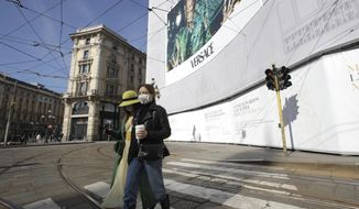 Women wearing sanitary masks walk in downtown Milan, Italy, Monday, Feb. 24, 2020. Italy has been scrambling to check the spread of Europe's first major outbreak of the new viral disease amid rapidly rising numbers of infections, calling off the popular Venice Carnival, scrapping major league soccer matches in the stricken area and shuttering theaters, including Milan's legendary La Scala. (AP Photo/Luca Bruno)