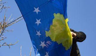 A municipality worker hangs Kosovo's flag to decorate the main street, during the 12th anniversary of the country's independence in the capital Pristina, Monday, Feb. 17, 2020. Kosovo declared independence from Serbia in 2008 recognized by more than 100 countries but not by Belgrade. (AP Photo/Visar Kryeziu)