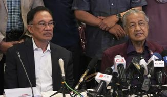 In this Feb. 22, 2020, photo, Malaysian Prime Minister Mahathir Mohamad, right, talks to media next to his successor Anwar Ibrahim in Putrajaya, Malaysia.  Political tension is building in Malaysia amid talks that Mahathir will pull his party out of the ruling alliance and team up with opposition parties to form a new government in a major political upheaval. It will thwart his named successor Anwar Ibrahim from taking over.(AP Photo/Vincent Thian)