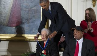 """In this Nov. 24, 2015, file photo, Willie Mays, right, looks on as President Barack Obama presents the Presidential Medal of Freedom to NASA mathematician Katherine Johnson during a ceremony in the East Room of the White House, in Washington. Johnson, a mathematician on early space missions who was portrayed in film """"Hidden Figures,"""" about pioneering black female aerospace workers, died Monday, Feb. 24, 2020. (AP Photo/Evan Vucci, File)"""
